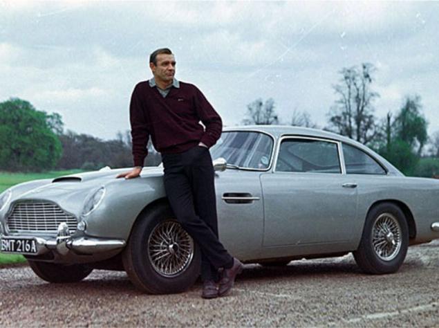 """Впервые DB5, оснащенный сменными номерными знаками, пулеметами, креслом-катапультой и другими разработками Отдела Q, появился в """"Голдфингере"""" 1964 года. Правда, литературный отец Агента 007 выбрал для него Aston Martin DB Mark III, но создатели экранизации предпочли только что вышедший DB5. Год спустя этот же автомобиль принял участие в съемках """"Шаровой молнии"""". Затем другие экземпляры модели предстали зрителям в еще девяти фильмах, включая """"Казино Рояль"""" и """"007: Координаты """"Скайфолл"""""""". DB5 выпускался всего три года: с 1963 по 1965, но его почти полувековая киноистория с лихвой компенсировала столь короткий срок производства. На подходе новые серии бондианы, и как знать, может быть, в октябре 2015 года мы вновь увидим на экранах старый добрый Aston Martin DB5, под завязку начиненный различными гаджетами, делающими этот автомобиль и его водителя всемогущими."""
