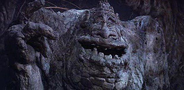 """Скалоед (Rock Biter). Монументальных размеров существо, одним из первых обитателей Фантазии появляется в кадре (пугая тех, кто его видит). Как выясняется, питается камнями — и чем они богаче всякими минеральными вкраплениями, тем ему радостнее. Для этого """"монстра"""" были изготовлены три модели. Самая крупная — сидячая, она же присутствует в фильме больше всего. Реальная её высота составила 1,6 метра, изготавливали её из крашеной пенорезины. Вторая модель — Скалоед верхом на своём """"передвижном устройстве"""", напоминающем одновременно асфальтный каток и детский велосипед. Как ни смешно, """"каменный каток"""" мог самостоятельно двигаться — в модель встроили мощный электромотор с приводом на переднюю ось, а батареи, от которых он питался, были установлены в седло. Модель самого скалоеда подвижной делать не понадобилось — только глаза и ноги. Их движением управляли удалённо. Вся комбинация весила порядка 100 кг."""