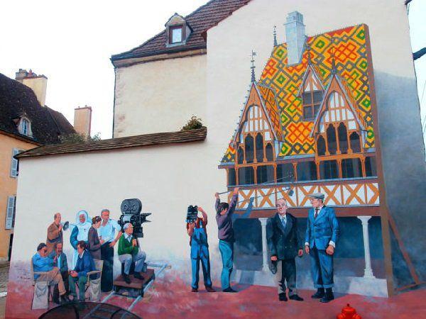 """А вот так благодарные французы увековечили память не только любимого актера, но и любимого фильма. На фреске на торце одного из домов городка Бон в Бургундии запечатлен момент съемок фильма """"Большая прогулка"""". Некоторые сцены комедии снимались в Боне в 1966 году, а фреска появилась там спустя 30 лет, в 1996."""